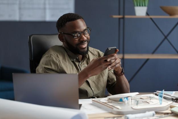 Молодой афроамериканец с помощью смартфона и улыбающийся счастливый бизнесмен с помощью текстовых приложений для мобильных телефонов ...