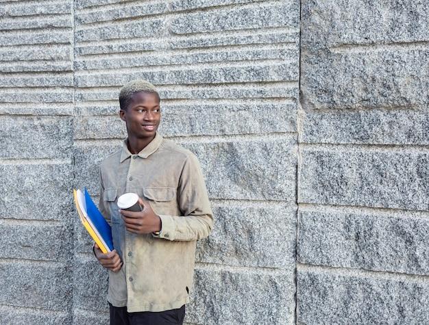 ノートブックとコーヒーを持つ若いアフリカ系アメリカ人の男