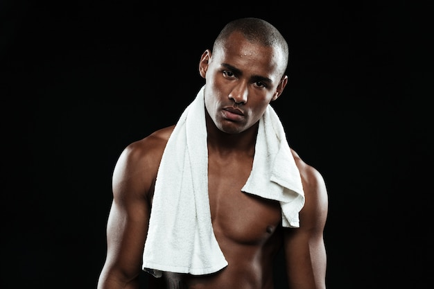 Young afroamerican sports man with white towel on his shoulders resting after workout,