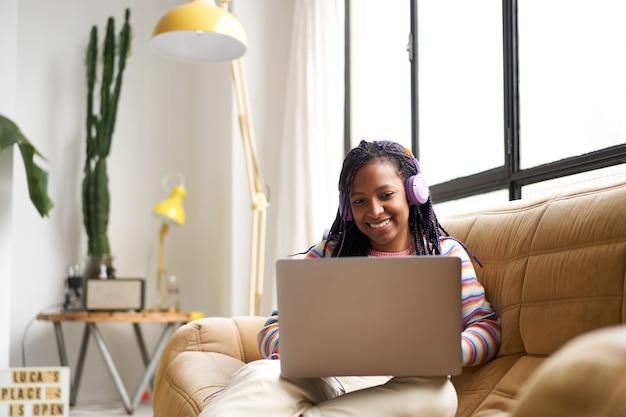チャットやインターネットサーフィンをするラップトップを使用して自宅からテレコミューティングする若いアフリカ系アメリカ人女性