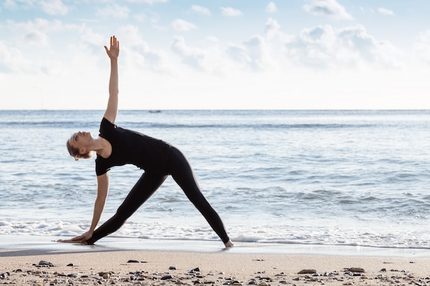 Young age woman in black doing yoga on sand beach