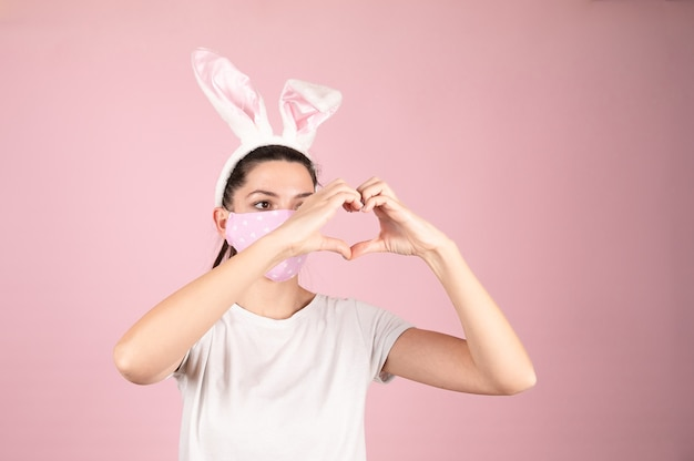 Женщина молодого возраста в маске защиты от коронавируса для эпидемии covid-19 делает форму символа сердца руками на розовом