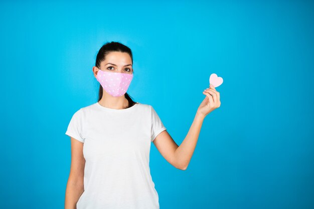 Женщина молодого возраста в маске защиты от коронавируса от эпидемии covid-19 держит в руке символ сердца.