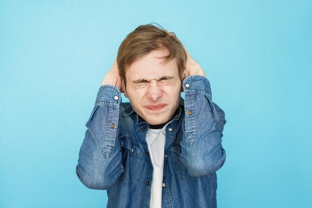 青の背景にデニムシャツの若い攻撃的な男性のティーンエイジャー