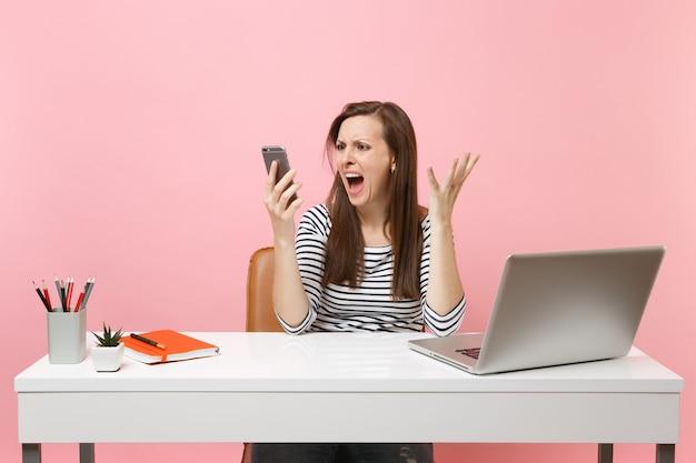 파스텔 핑크색 배경에서 격리된 pc 노트북을 들고 사무실에 앉아 일하는 동안 휴대전화로 소리를 지르는 젊은 공격적인 여성. 성취 비즈니스 경력 개념입니다. 공간을 복사합니다.