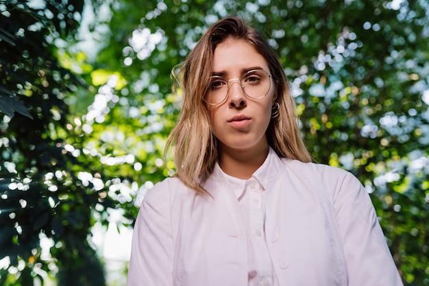 温室で働く若い農業エンジニア。カメラを見て若い女性科学者