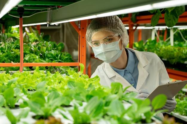 고글, 마스크, 모자를 쓴 젊은 농공학자는 수직 농장 온실에 서서 클립보드에 녹색 묘목에 대해 메모합니다.