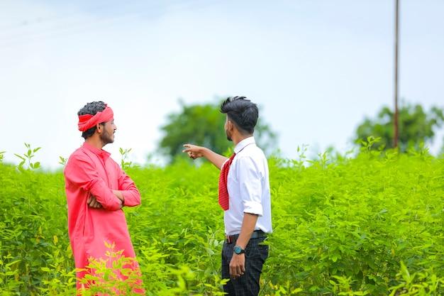若い農学者がグリーンフィールドで農民と話し合う