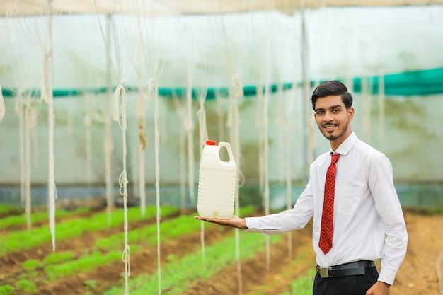 温室でボトルを手に持っている若い農学者