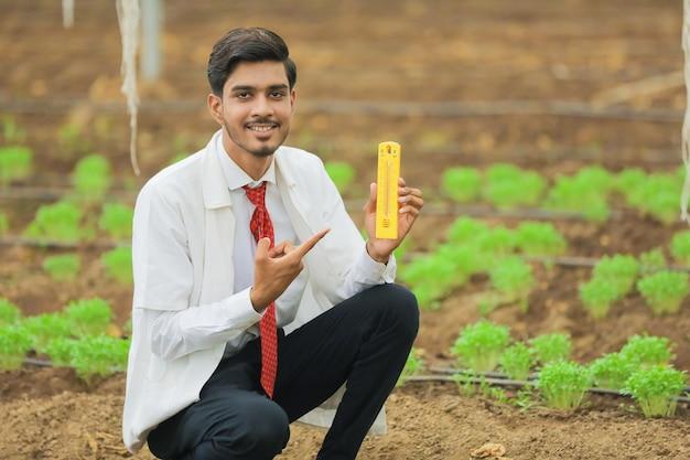 温室で観察している若い農学者
