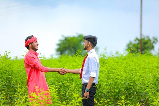 若い農学者が畑でインドの農民と手を振る
