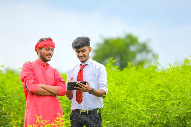 グリーンフィールドで農民にタブレットでいくつかの情報を示す若い農学者