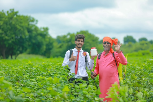 Young agronomist with farmer showing fertilizer botle in field