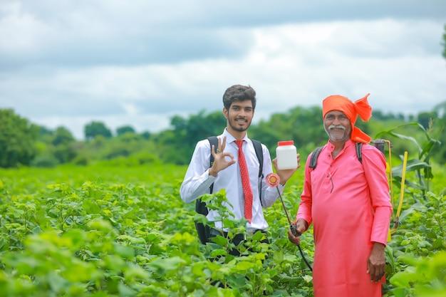 畑で肥料の瓶を見せている農夫と若い農学者