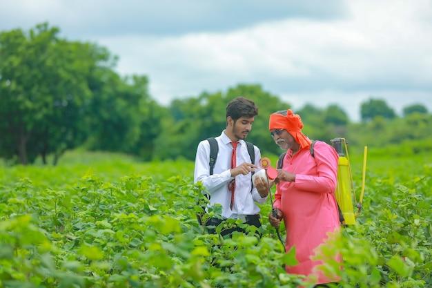 Молодой агроном с фермером показывает бутылку удобрений в поле
