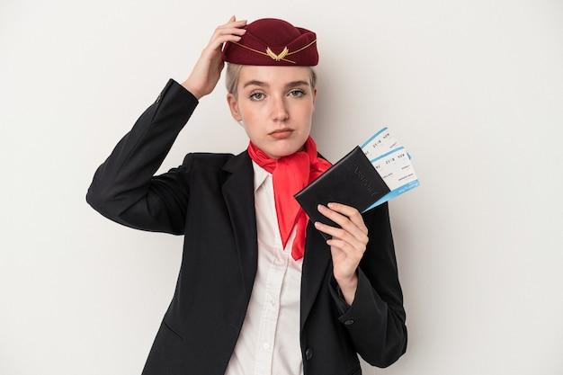 ショックを受けている白い背景で隔離のパスポートを保持している若いエアホステス白人女性、彼女は重要な会議を覚えています。