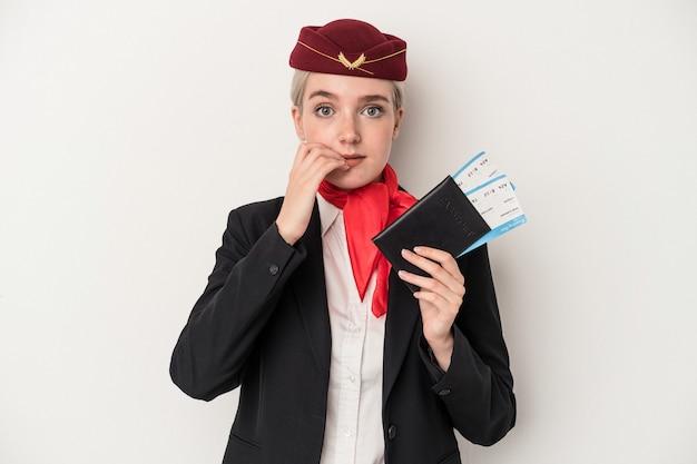指の爪を噛んで、神経質で非常に心配している白い背景で隔離のパスポートを保持している若いエアホステス白人女性。