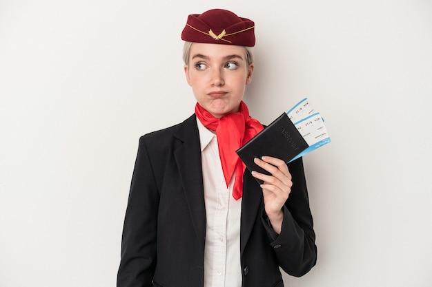 白い背景で隔離のパスポートを保持している若いエアホステス白人女性は混乱し、疑わしく、不安を感じています。