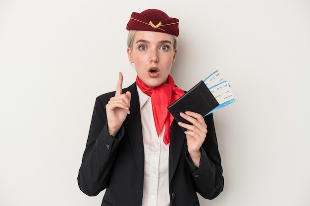 アイデア、インスピレーションの概念を持つ白い背景で隔離のパスポートを保持している若いエアホステス白人女性。