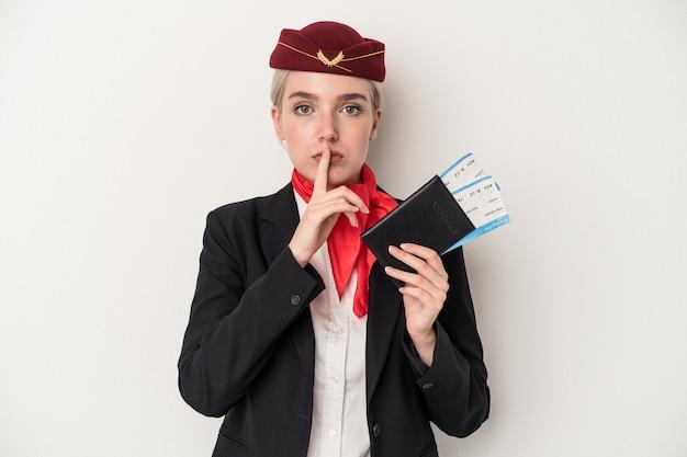 秘密を保持するか、沈黙を求めて白い背景で隔離のパスポートを保持している若いエアホステス白人女性。