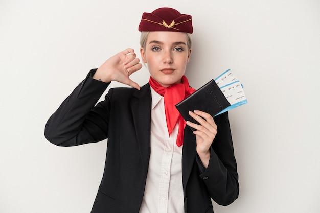 嫌いなジェスチャーを示す白い背景で隔離のパスポートを保持している若いエアホステス白人女性、親指を下に。不一致の概念。
