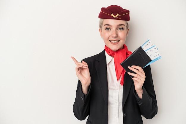 若いエアホステス白人女性は、白い背景で隔離のパスポートを持って微笑んで脇を指して、空白のスペースで何かを示しています。
