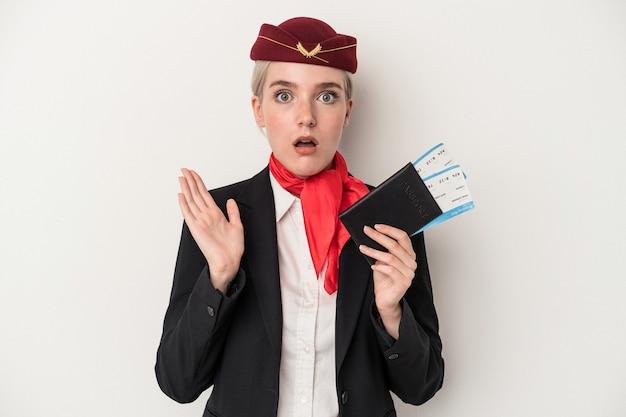 白い背景で隔離のパスポートを保持している若いエアホステス白人女性は驚いてショックを受けました。