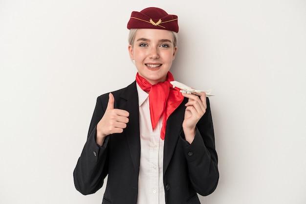 白い背景で隔離の飛行機を保持している若いエアホステス白人女性