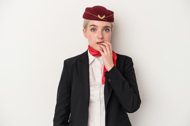 若いエアホステス白人女性は、白い背景で爪を噛んで孤立し、神経質で非常に心配しています。