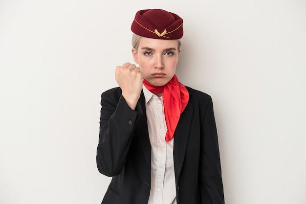 カメラに拳、積極的な表情を示す白い背景で隔離の若いエアホステス白人女性。