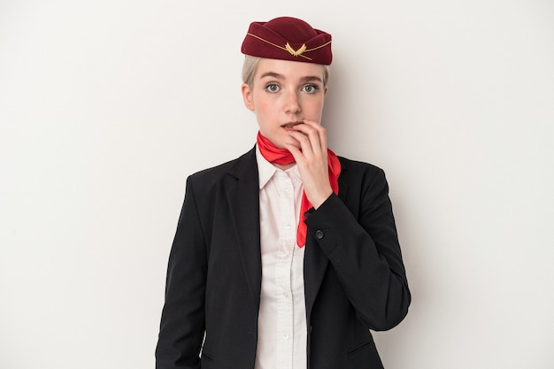 Young air hostess caucasian woman isolated on white background biting fingernails, nervous and very anxious.