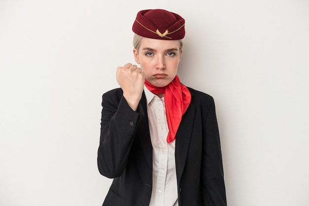Young air hostess caucasian woman isolated on white background showing fist to camera, aggressive facial expression.