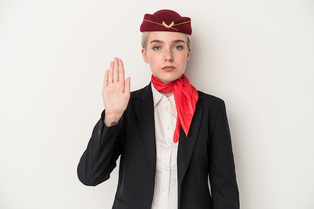 Young air hostess caucasian woman isolated on white background standing with outstretched hand showing stop sign, preventing you.