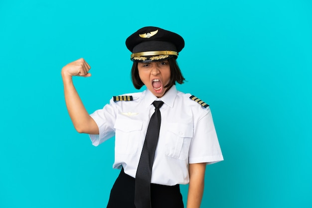 Young airplane pilot over isolated blue background celebrating a victory