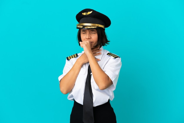 Young airplane pilot over isolated blue background coughing a lot