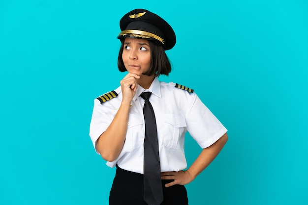 Young airplane pilot over isolated blue background having doubts and thinking