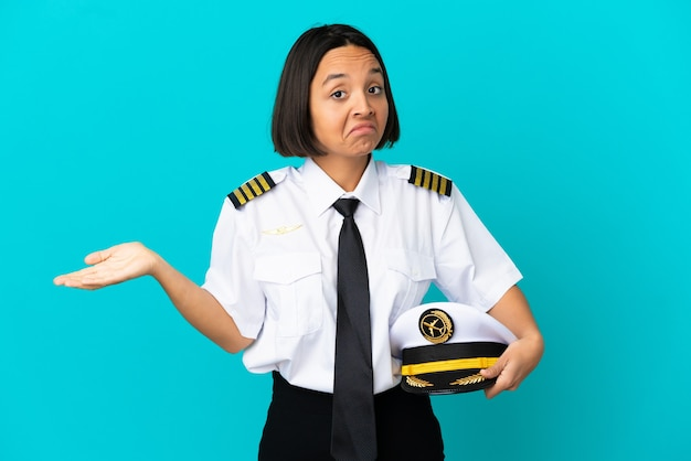 Young airplane pilot over isolated blue background having doubts
