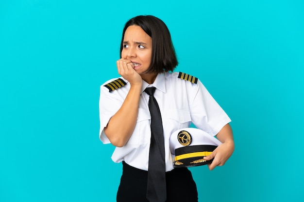 Young airplane pilot over isolated blue background is a little bit nervous
