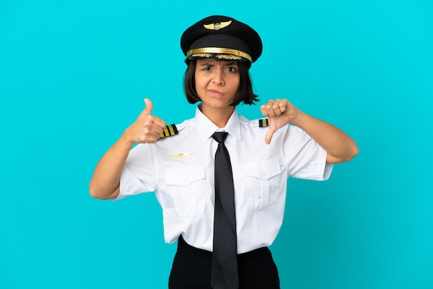 Young airplane pilot over isolated blue background making good-bad sign. undecided between yes or not