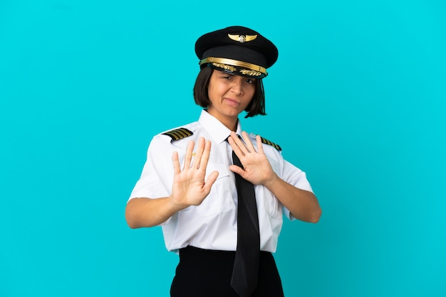 Young airplane pilot over isolated blue background nervous stretching hands to the front