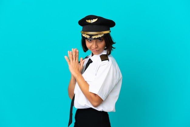 Young airplane pilot over isolated blue background scheming something
