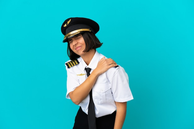 Young airplane pilot over isolated blue background suffering from pain in shoulder for having made an effort