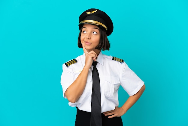Young airplane pilot over isolated blue background thinking an idea while looking up