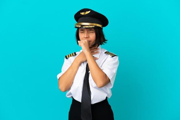 Молодой пилот самолета на изолированном синем фоне много кашляет