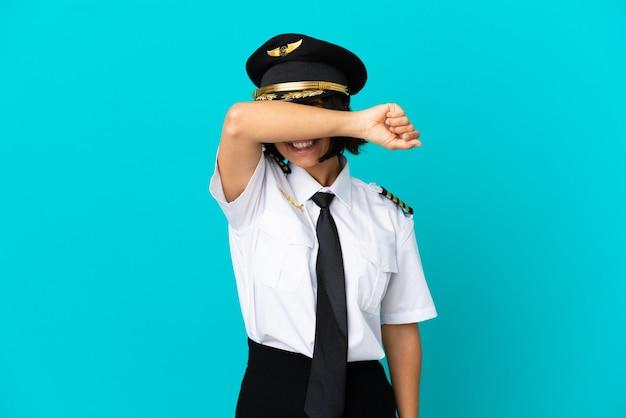 Молодой пилот самолета на изолированном синем фоне, закрывая глаза руками