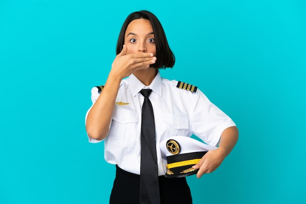 손으로 입을 덮고 고립 된 파란색 배경 위에 젊은 비행기 조종사