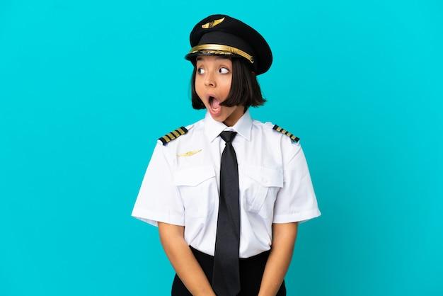 외진 파란색 배경 위에 있는 젊은 비행기 조종사가 옆을 바라보면서 깜짝 제스처를 하고 있다