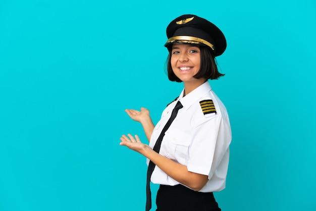 Молодой пилот самолета на изолированном синем фоне, протягивая руки в сторону, приглашая приехать