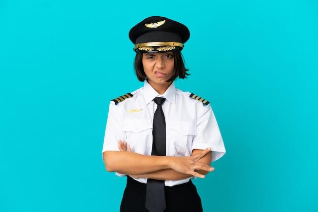 孤立した青い背景の上の若い飛行機のパイロットは動揺を感じています