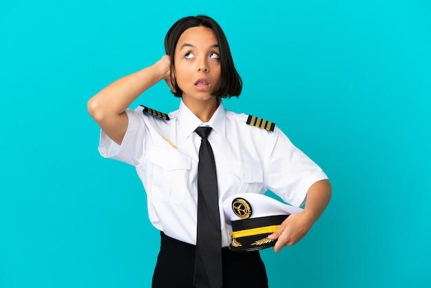 欲求不満と耳を覆っている孤立した青い背景の上の若い飛行機のパイロット